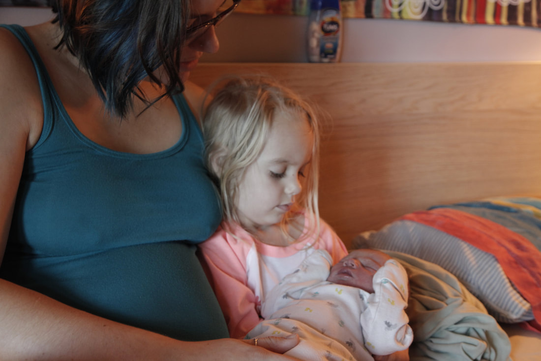 Big sister holding new baby.